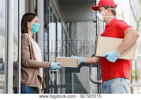 Fast Delivery To Door During Quarantine. Courier In Medical Mask And Gloves Gives Box To Client, On