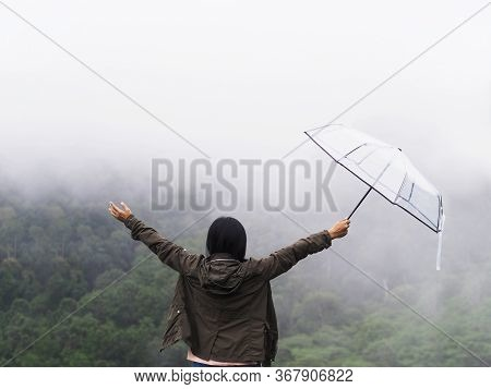 Back View Happy Woman Tourist Raise Arm And Hold Umbrella Over Green Rain Forest At High Mountain In