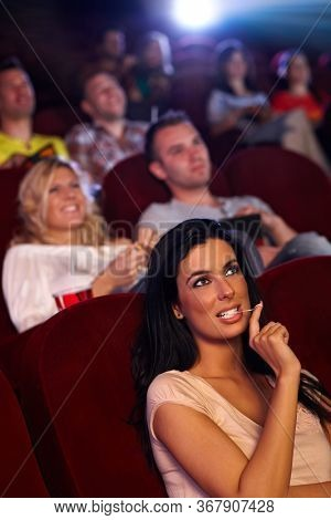 Pretty young girl sitting in multiplex movie theater, watching movie, playing with chewing gum.