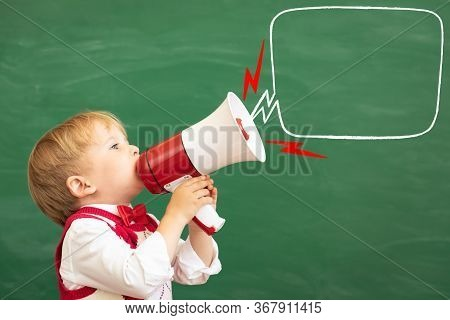 Bright Idea! Funny Child Student Speaking By Megaphone In Class. Happy Kid Shouting By Loudspeaker A