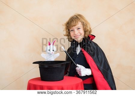 Child Magician Holding A Top Hat With Toy Rabbit