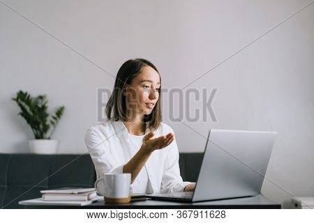 Happy Young Woman Sitting At The Table And Using Laptop, Calling By Video Chat. Freelance And Workin