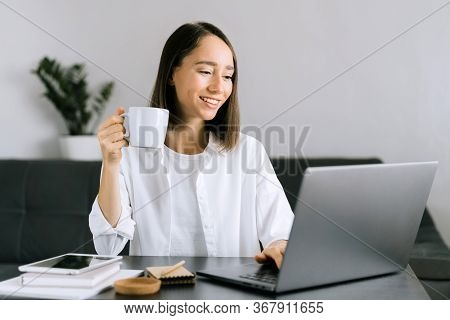 Happy Young Woman Sitting At The Table, Holding Pink Cup Of Coffee Or Tea And Using Laptop, Calling