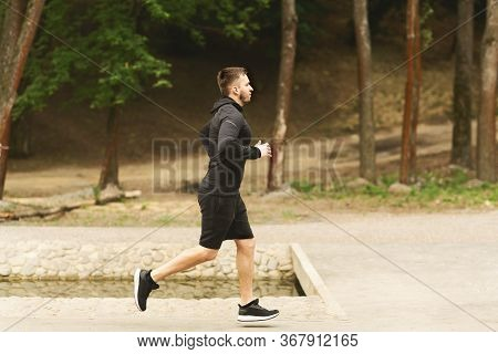 Side View Full Length Portrait Of Focused Jogging Man Running In Park, Copy Space, Blurred Backgroun