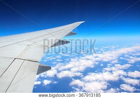 Traveling concept. Aerial view of cloudscape. Looking Out the Window of a Plane. Scenic view with wing of an airplane