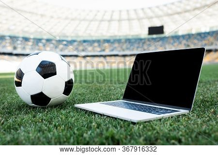 Soccer Ball And Laptop With Blank Screen On Grassy Football Pitch At Stadium