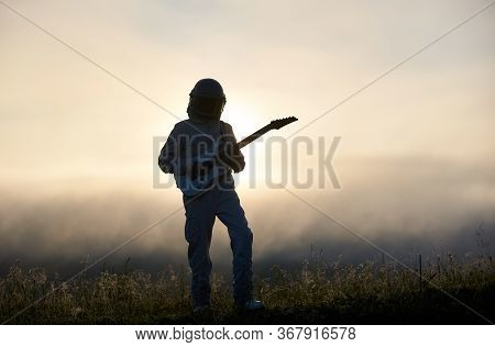 Silhouette Of Space Traveler Playing Melody On Guitar In Misty Grassy Valley With White Mystical Sky