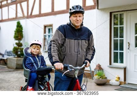 Portrait Of Little Toddler Girl With Security Helmet On The Head Sitting In Bike Seat And Her Father