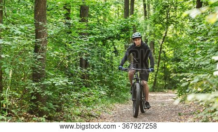 Young Cyclist Riding Professional Bike By Mountain Forest Trail, Panorama With Empty Space