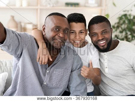 Smiling Senior Black Man Taking Selfie With His Son And Grandson At Home, Posing To Camera Together,