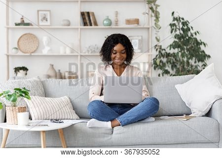 Remote Work. Millennial African American Woman Working On Laptop At Home, Sitting On Couch In Living