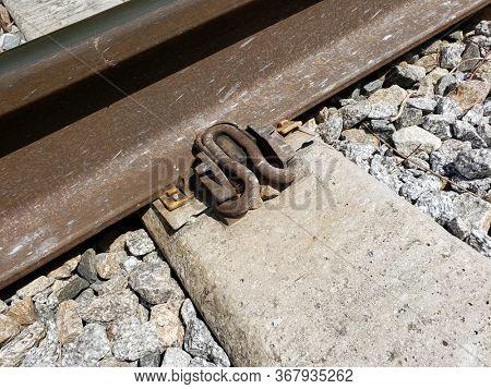 Concrete railway tie over gravel.