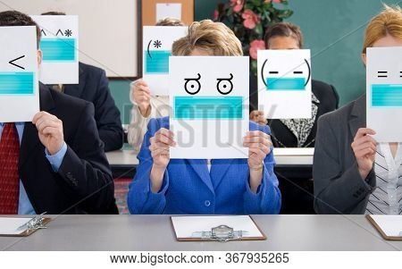 Group of business woman and men sitting at table with keyboard shortcut faces wearing face mask.