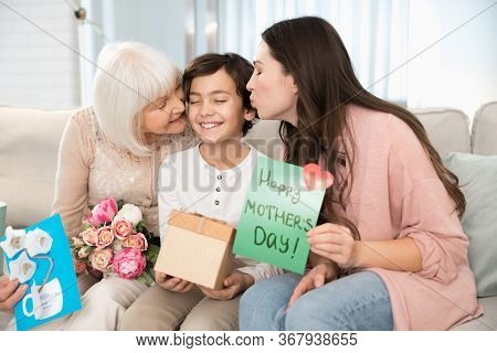 Blissful Boy Being Kissed By His Female Parent And Grandma