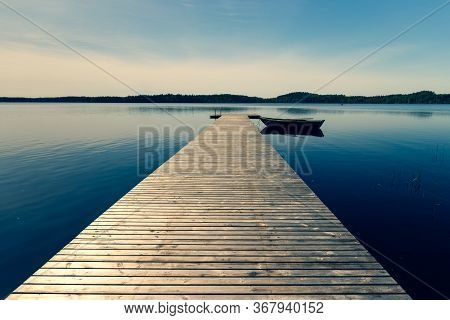 A Wooden Boat With Oars Moored To A Pier On A Lake In Spring. The Pier From The Planks Leaves With T