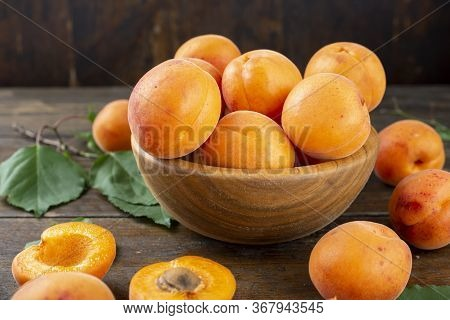 Ripe Apricots In A Wooden Plate On The Table, On Wooden Background. Next To Apricots Green Leaves