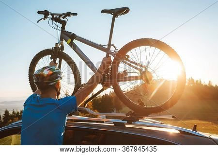 Young Man Dresses Modern Cycling Clothes And Protective Helmet Installing His Mountain Bike On The C
