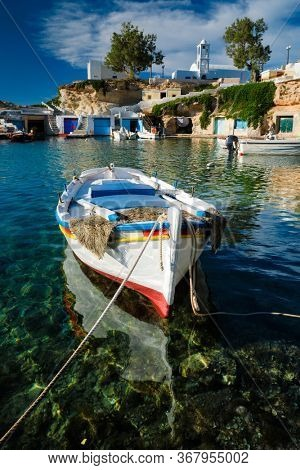Fishing boars moored in crystal clear turquoise sea water in harbour in Greek fishing village of Mandrakia, Milos island, Greece. Horizontal camera pan