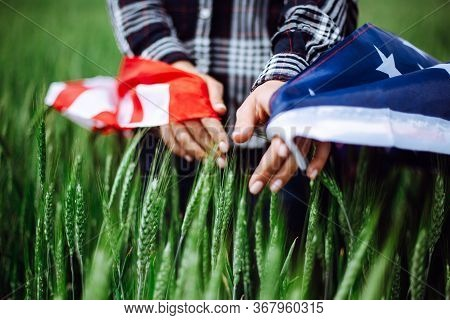 Womans Hands With An American Flag Touches Spikelets On The Green Wheat Field. Patriotic Holiday Cel