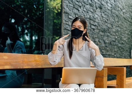 Asian Woman Wearing A Face Mask Outside While Sitting On Laptop And Pointin At Her Mask. Dont Forget