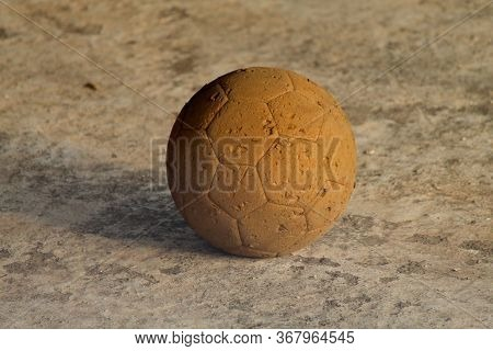 Soccer Ball Very Old, Muddy, Dusty And Worn Out Isolated On The Ground