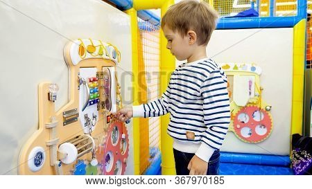 Cute Little Boy Playing With Buttons And Knobs On Educational Childs Board In Kindergarten