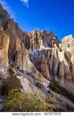 Clay Cliffs. Grandiose natural land formations. Jagged sharp pinnacles and ridges separated by narrow ravines. New Zealand, South Island. The concept of extreme, natural and photo tourism