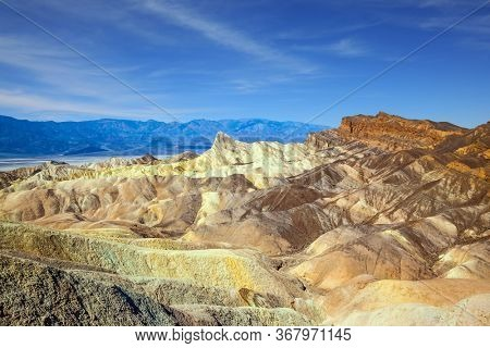 Magnificent erosion landscape of various shades. Zabriskie Point is part of the Amargosa Range. Death Valley in California, USA. Sunset. The concept of active, extreme and photo tourism