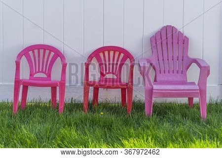 Three Miniature Childrens Colourful Plastic Chairs On The Lawn Against A White Wooden Fence