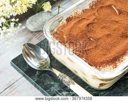 Traditional Coffee Tiramisu Dessert With Mascarpone Cheese And Cocoa Powder In Glass Container On Gr