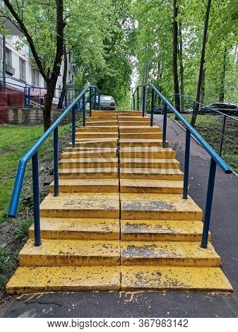 Old Shabby Metal Staircase In Yellow. Uneven Steps. Unfriendly Urban Environment For The Disabled.