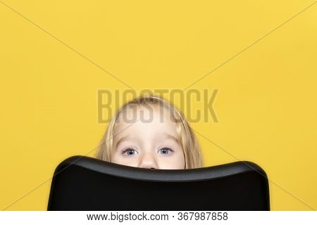 Funny And Pretty Child Girl With Long Fair Hair Peeks Out From Behind A Chair. The Child Is Hiding B