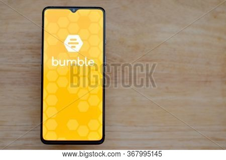 London, England, United Kingdom, 2020. Flat Lay With Wooden Background And Bumble App Logo On Displa