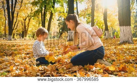 Little Boy With Young Mother Picking Up Yellow And Red Mapple Tree Leaves In Autumn Park