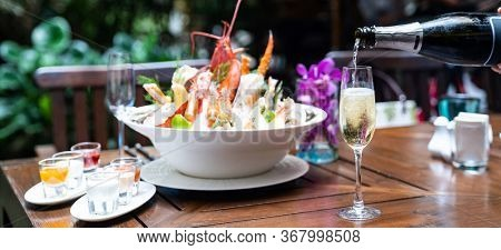 Panoramic web banner Waiter pouring white wine to wine glass and serving to customer in restaurant with big bowl seafood on ice in background. Restaurant gastronomy food and drink consumerism concept.