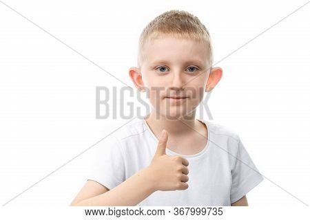 Little Boy Shows Thumb Up On White Isolated Background. Backlight Vertical Photo. Child Shows Finger