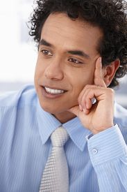 Portrait of young afro-american businessman in blue shirt looking away, hand on chin, smiling.