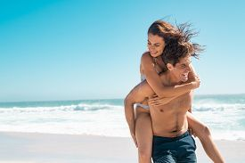 Young couple enjoying vacation at beach, copy space. Portrait of mid smiling man carrying girlfriend on his back along the sea shore. Boyfriend giving piggyback ride to happy woman having fun together
