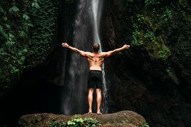 Back View Of A Man Standing By Waterfalls With Arms Outstretched. Man At Waterfall Raising His Hands