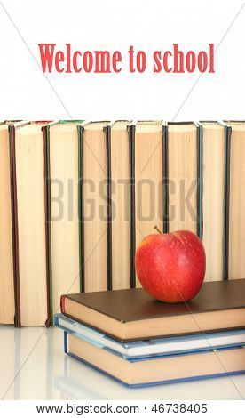 pile of books with an apple on white background close-up