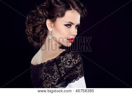 Fashion Brunette Model Portrait. Jewelry and Hairstyle. Elegant lady Isolated on black background.
