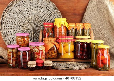 Different conservations on shelves on wooden background