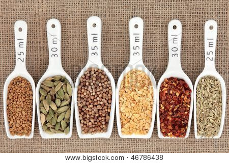 Spice selection in white porcelain scoops with metric measurement over hessian background.
