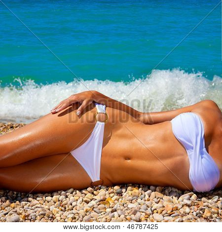 A Woman Sunbathes On A Beach