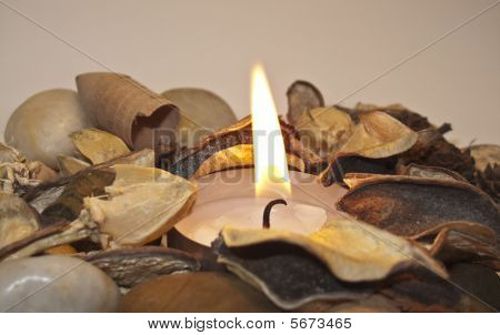 A candle flame surrounded by stones and popuri poster