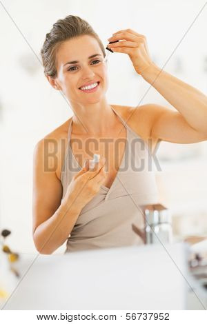 Young Woman Applying Cosmetic Serum In Bathroom