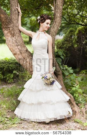 Young Bride With Bouquet Near Tre