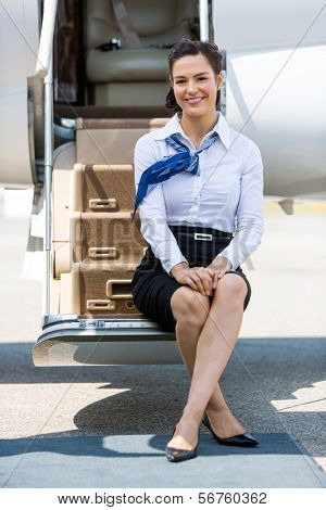 Full length portrait of beautiful stewardess sitting on ladder of private jet