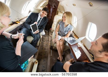 Businessman showing project on digital tablet to partners in private plane