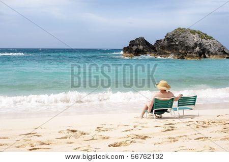 Elderly woman sitting at the beach